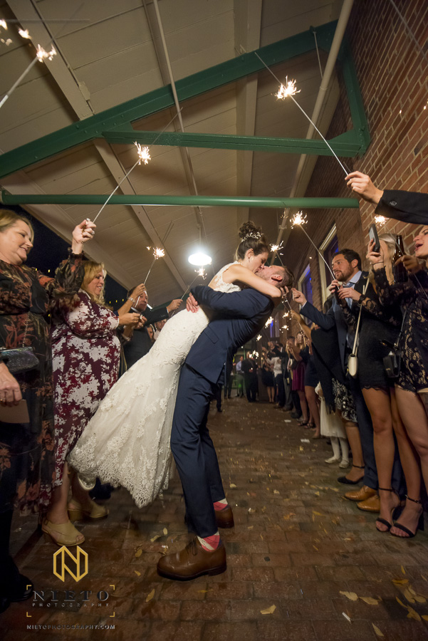 the groom kissing his wife during their sparkler exit at Market Hall