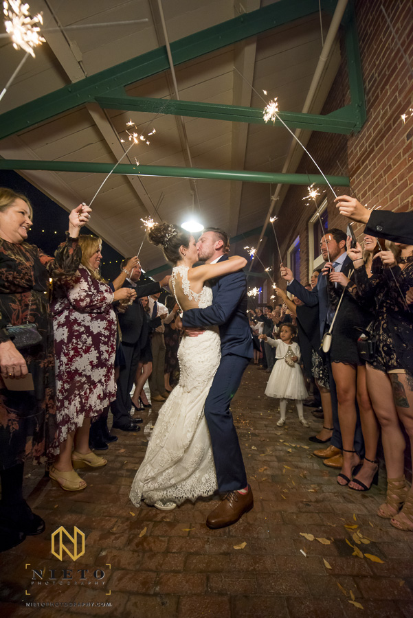 the bride and groom kissing during their sparkler exit at Market Hall