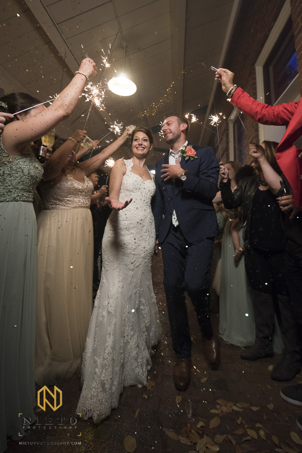 the bride and groom being showered with glitter during their sparkler exit at their market hall wedding reception