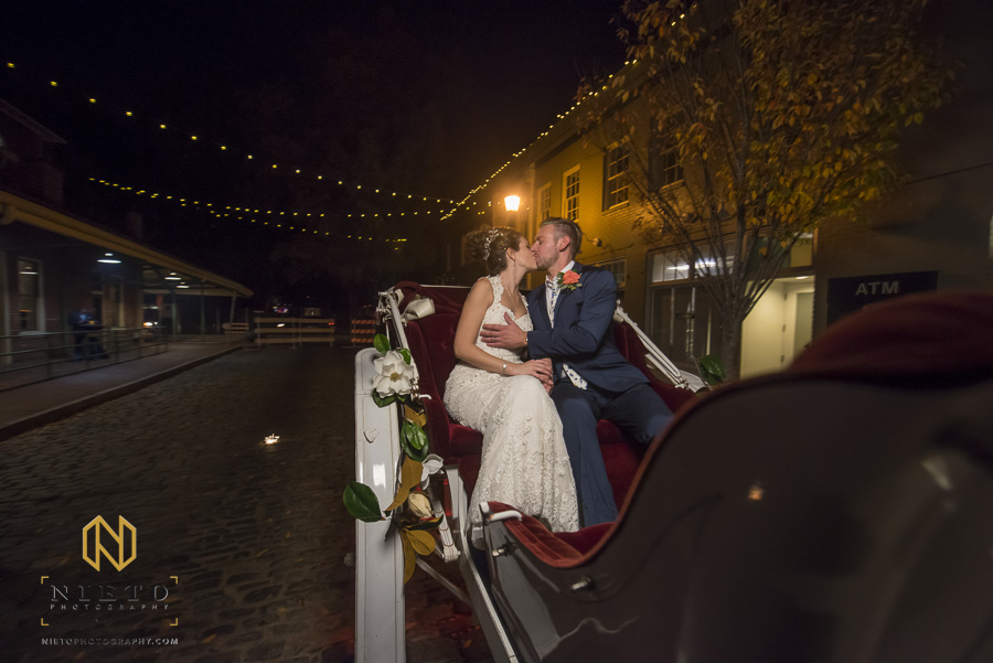 the bride and groom kissing as they ride in their horse drawn carriage