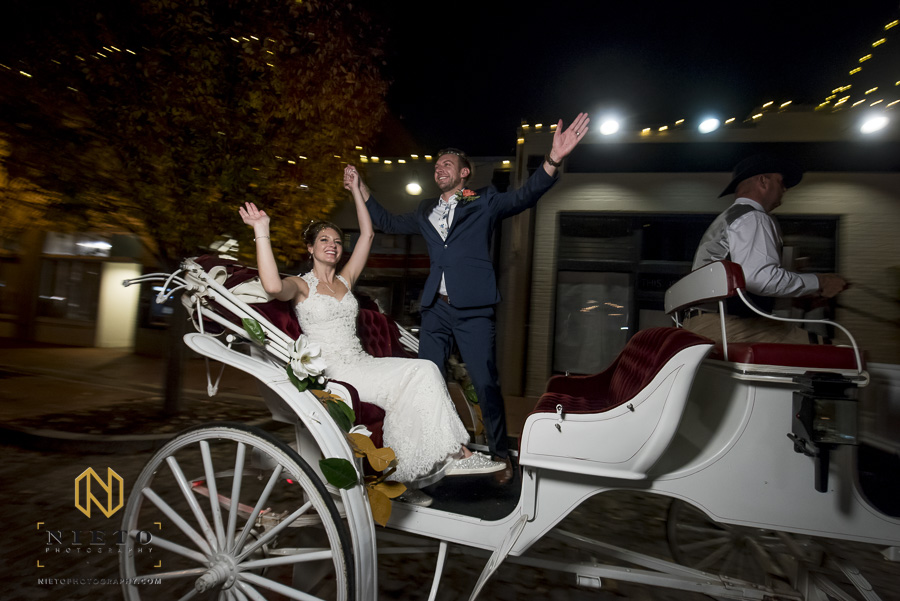 the groom standing on the horse drawn carriage outside of market hall