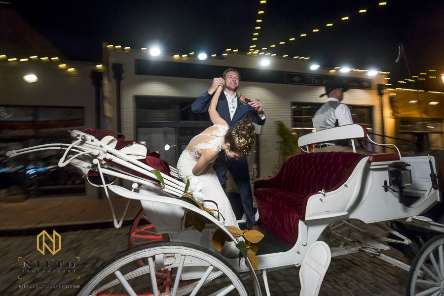 the bride bowing with the groom holding her hand as they ride on their horse drawn carriage