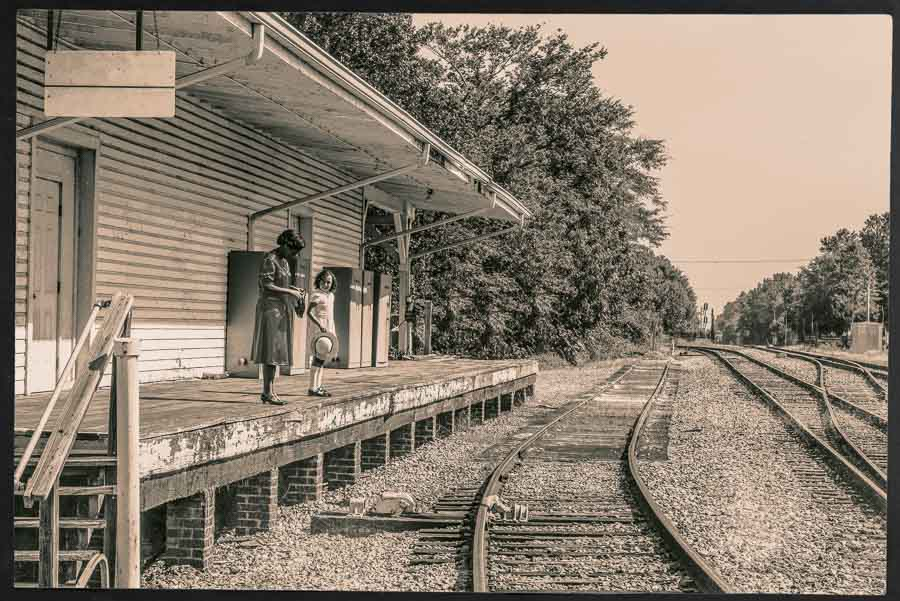 sepia tinted image of a mother and daughter waiting for a train at Apex Union Depot