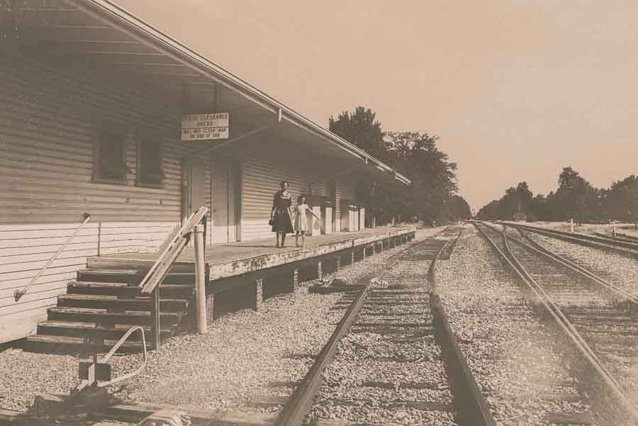 sepia image of a mother at daughter standing at an empty Apex Union Depot