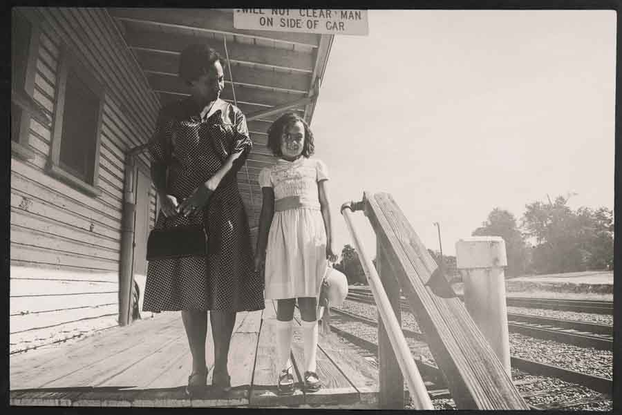 black and white tinted image of a mother and daughter standing on a train platform in Apex NC