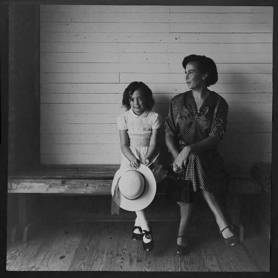 old black and white image of a little girl and her mother dressed up sitting on a wooden bench in Apex