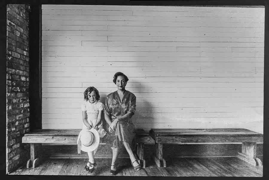 black and white picture of an angry little and her mother waiting on a wooden bench on Mother's Day