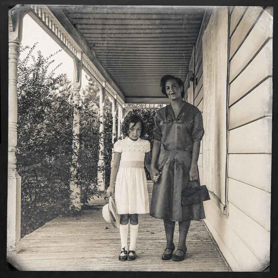black and white tinted image of a mother and daughter dressed nicely standing on the porch of a house in Apex NC