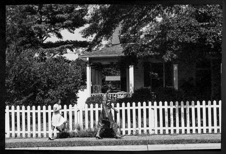 black and white image of a mother walking by a picket fence and her daughter skipping behind her on Mothers Day