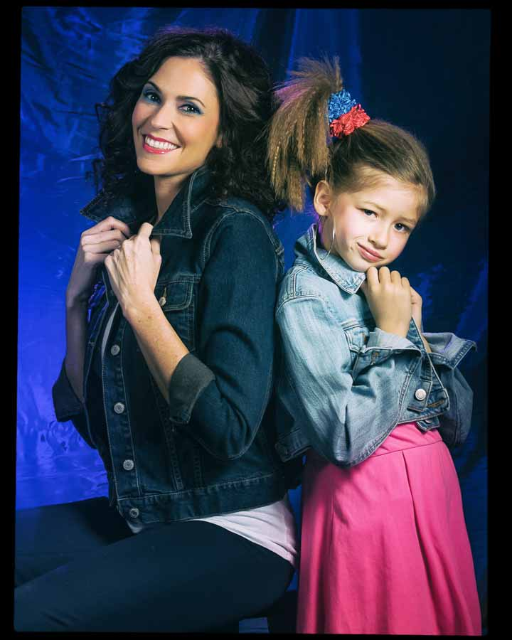 mother and daughter posing together in denim jackets for a 1980s glamour shot