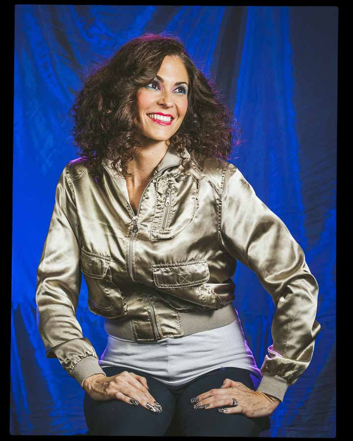 woman posing for a glamour shot with a blue background and wearing a gold jacket