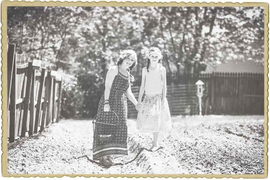 faded black and white image with a frame around it of a mother and daughter taking a picture together