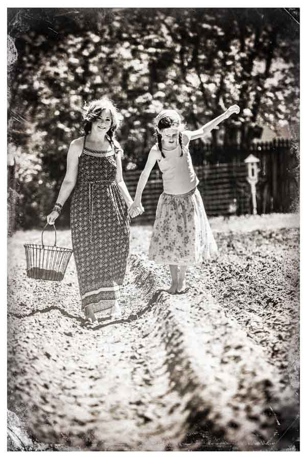 black and white image of a mother and daughter walking in plowed field