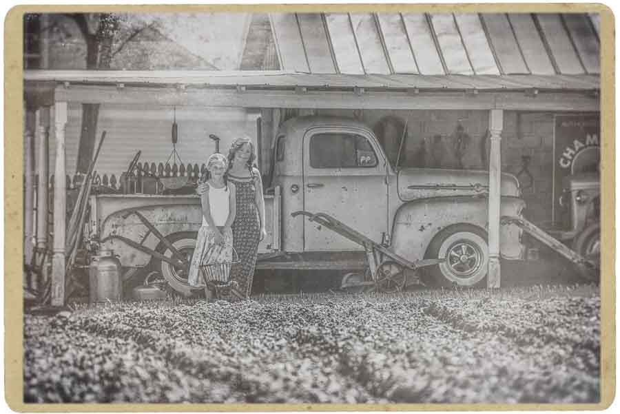 faded black and white image of a mother and daughter standing in front of an old truck in a barn