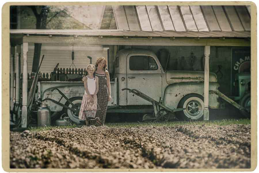 hand colored image of a mother and daughter standing in front of an old truck in a barn