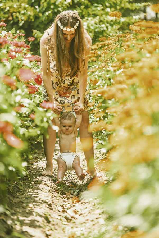 mother walking her diapered baby daughter though a field of red and yellow flowers