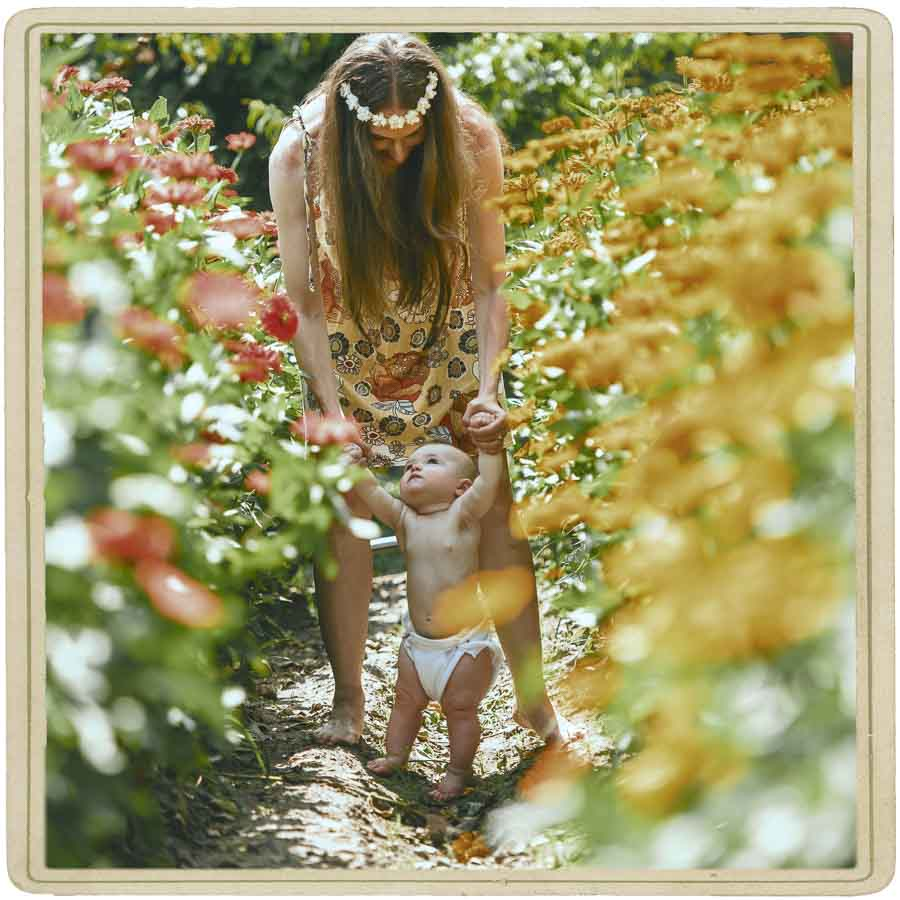 baby girl in cloth diaper looking up at her mother as the stand together in a flower field