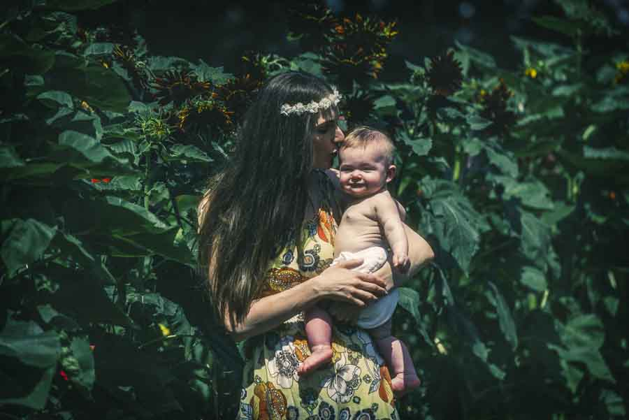 hippie mother kissing her baby daughter on the head as the baby smiles for the camera