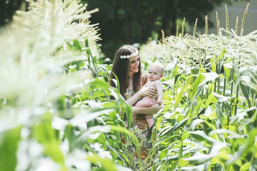 mother carrying her naked infant daughter through a corn field in Apex NC