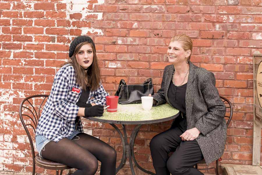 daughter ignoring mother as her mother smiles at her while they sit for coffee