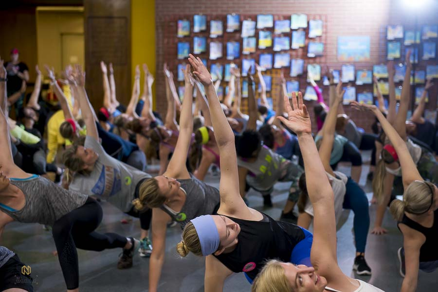 workout guest stretching with their hands in the air during the cool down period of the Raleigh group fitness winter workout