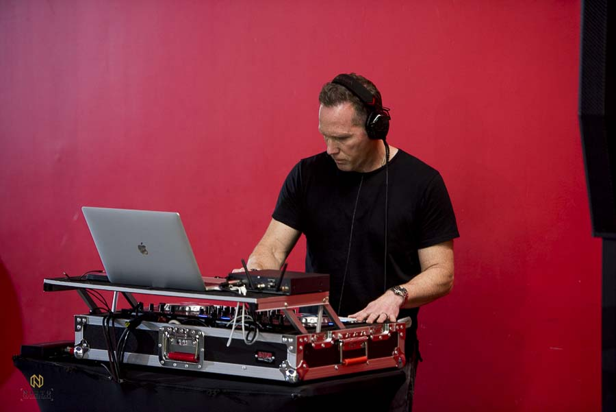 Joe Bunn of Bunn DJ company playing music against a red wall