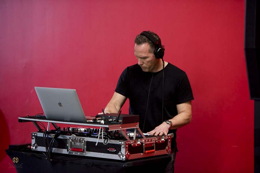 Joe Bunn of Bunn DJ company playing music against a red wall