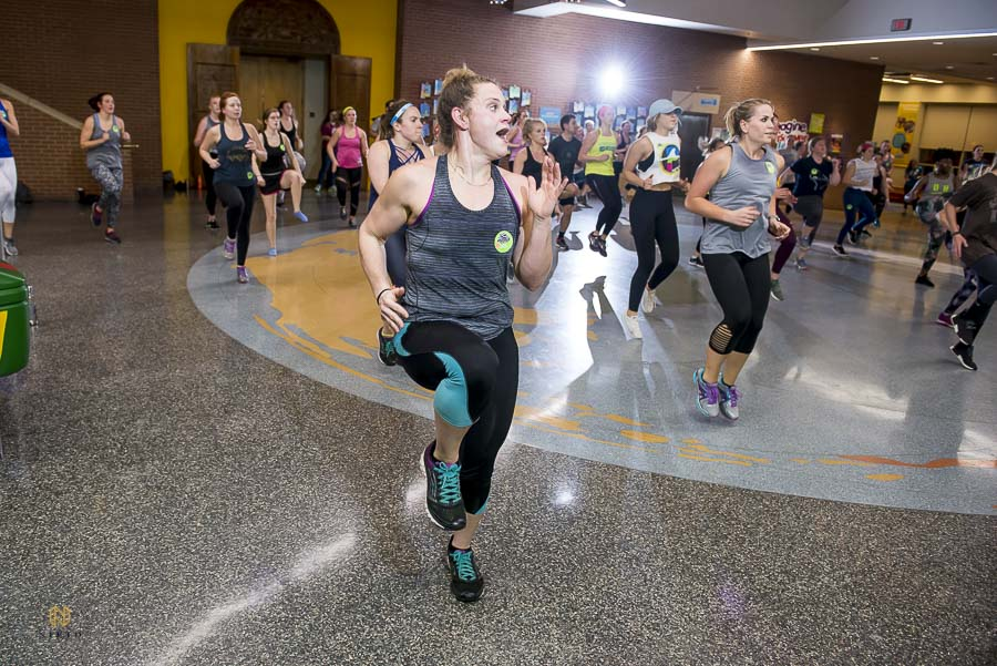 Raleigh Group Fitness guest high stepping her legs during the main room work out at Marbles Museum