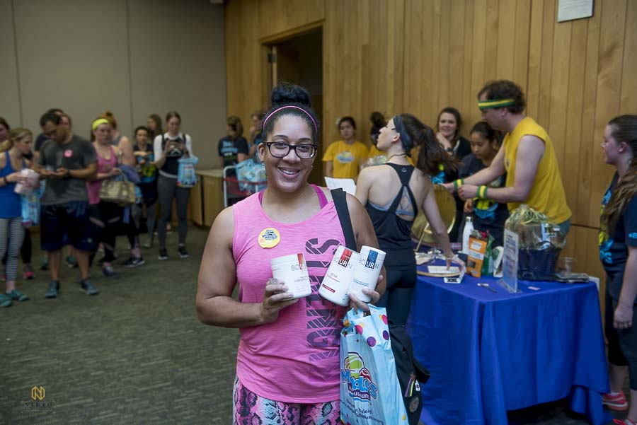 work out guest holding her raffle prize and smiling for the camera