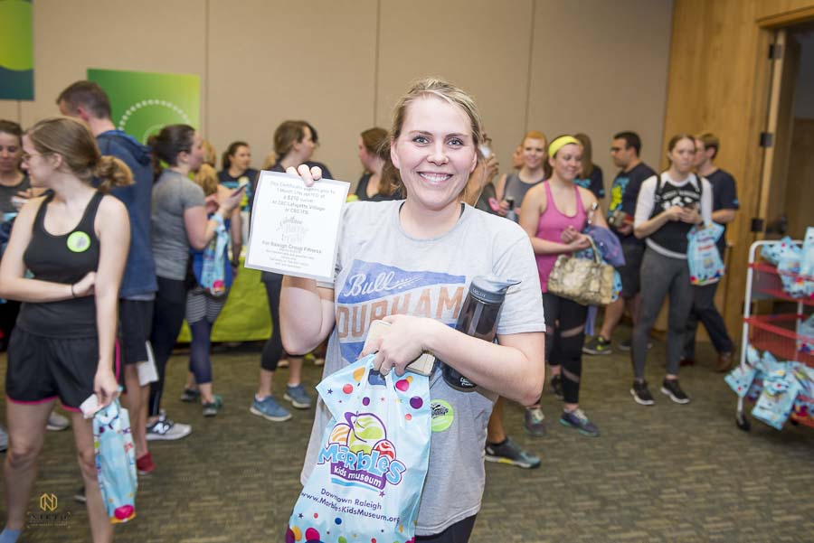 Guest holding her swag bag and raffle win at Marbles Kids Museum