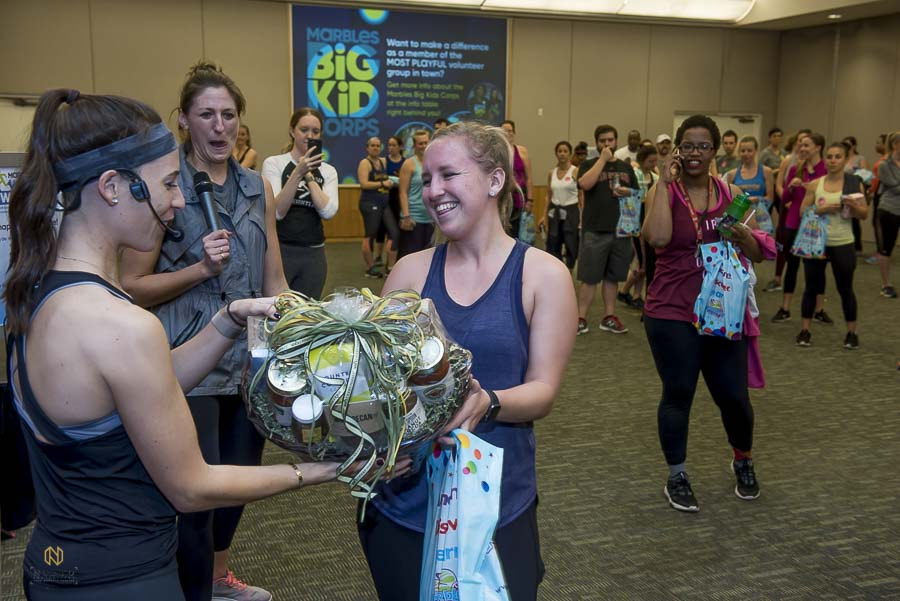 work out guest receiving her raffle prize from Whole Foods