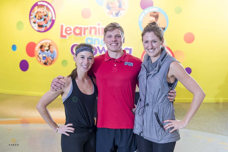 group shot of Ashley Liu Kirkman, brittany, and Conner smiling in front of the yellow wall at Marbles Kids Museum.