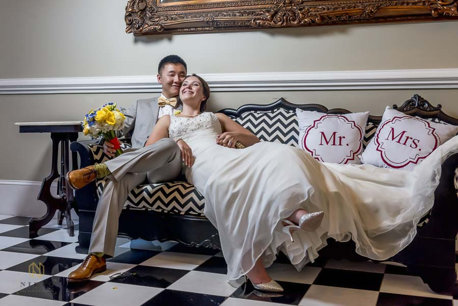 Bride reclining into her groom as they sit together on the couch at the Garden on Millbrook posing for their Raleigh Wedding Photographer