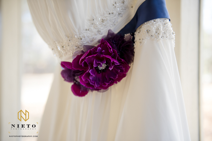 purple flowers on the wedding gown sash