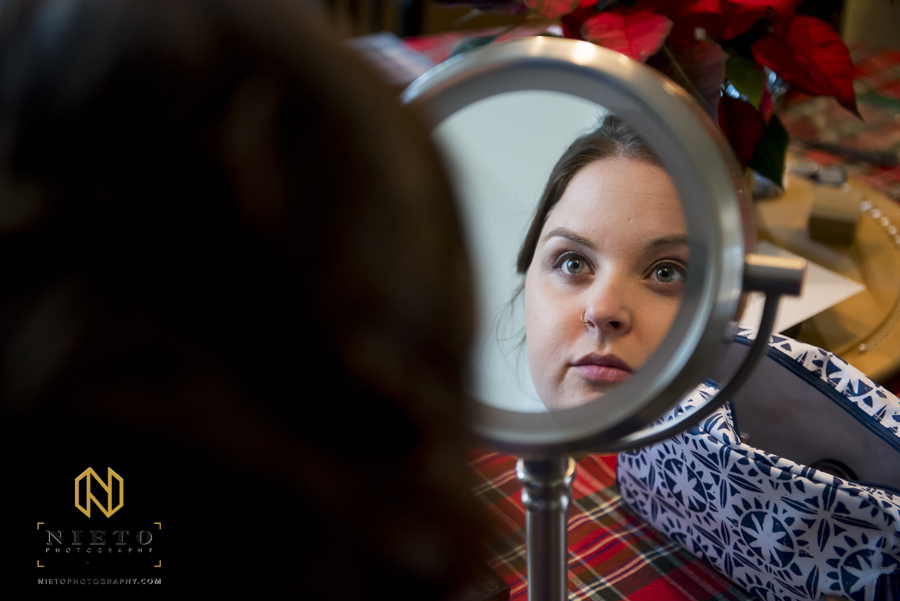 bride looking at her reflection in a makeup mirror