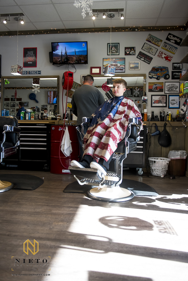 grooms son sitting in the barbers chair waiting to have his hair styled at Van-tique in Garner