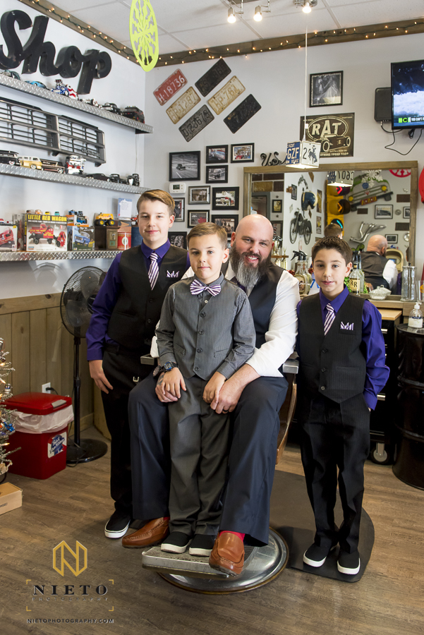 The groom sitting in a barbers chair surrounded by his sons in side of Van-tique-barbershop