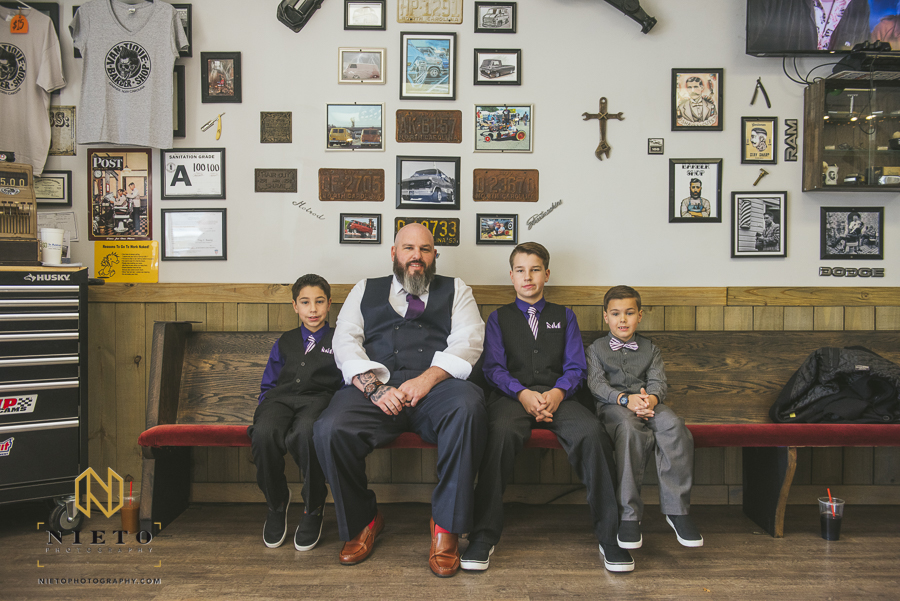 the groom and his young sons sitting on a bench smiling for a portrait inside of Van-tique-barbershop in Garner NC
