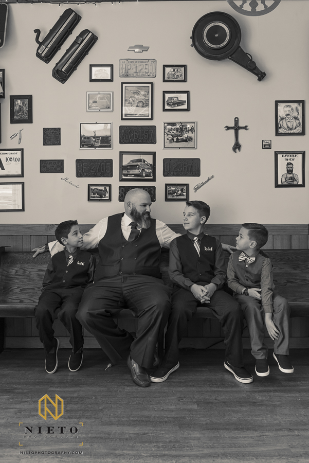 Black and white portrait of father and young sons inside of Van-tique-barbershop