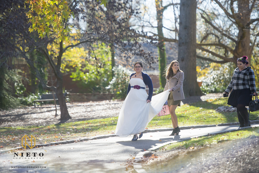 Bride walking in Mordecai Historic park with her friend holing her dress