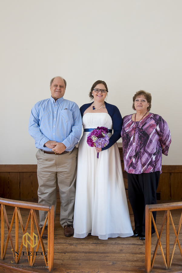 Bride standing with her parents at the altar inside of St. Mark's Chapel