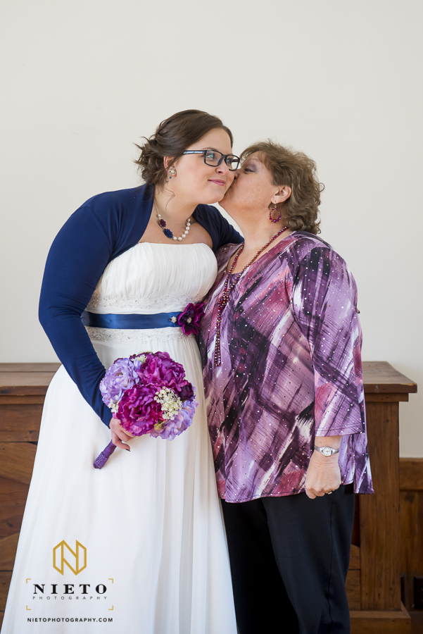 mother of the bride giving a kiss to the bride