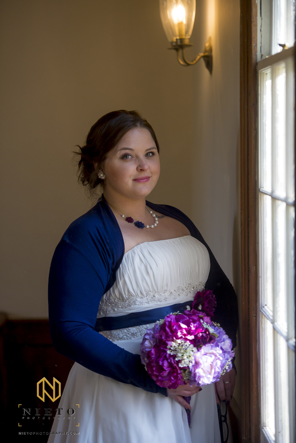 bride standing near window posing for portrait in St Mark's Chapel