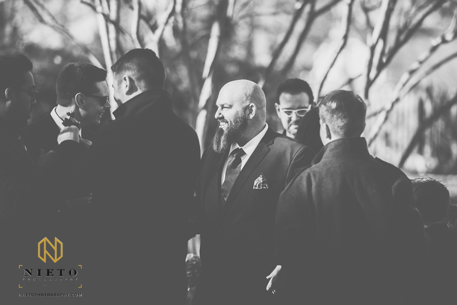 black and white image of groom smiling at another groomsman