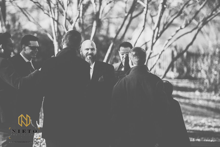 black and white image of the groom talking to his groomsmen at Mordecai Historic Park