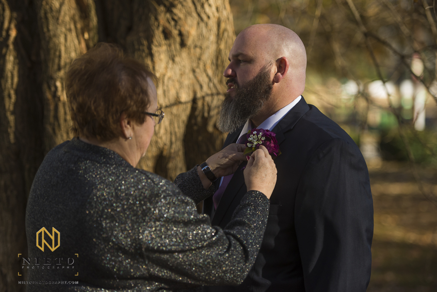 the mother of the groom pinning his boutonniere on his lapel