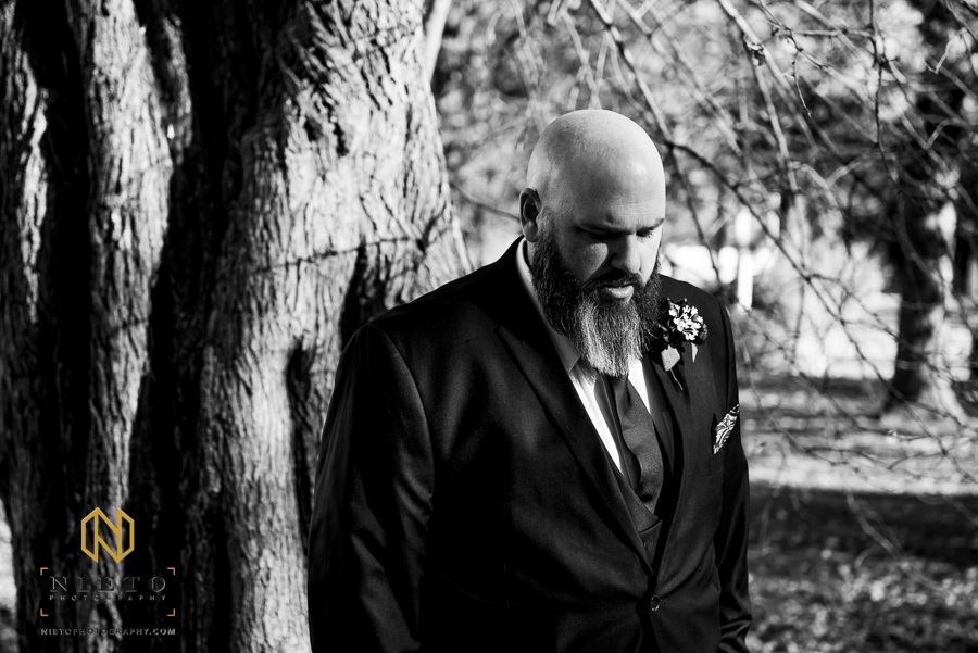 black and white picture of the groom standing by himself before the first look