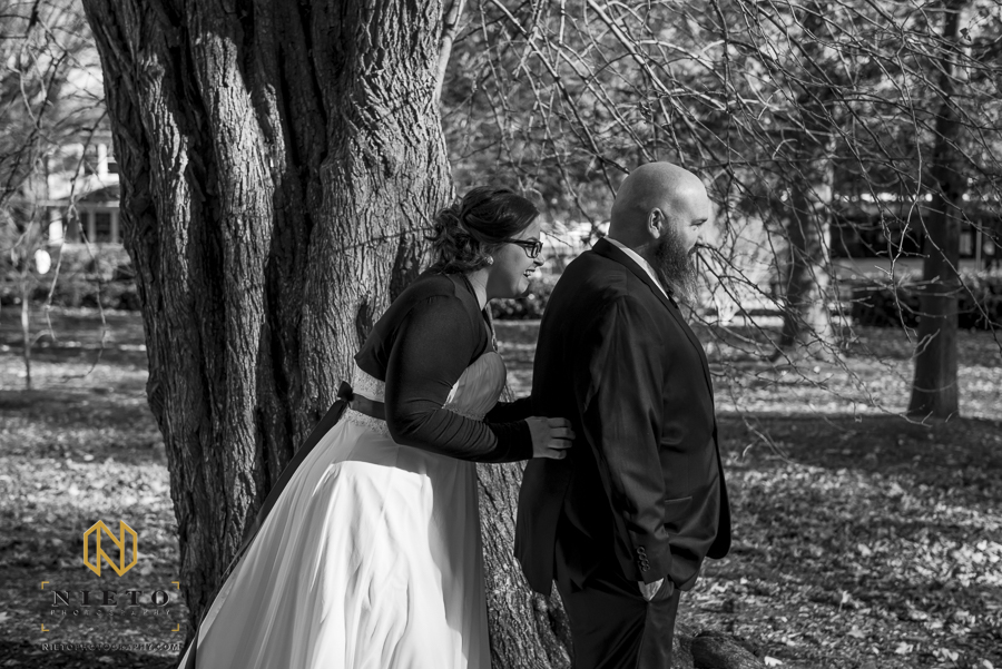 black and white picture of the bride standing behind the groom during their first look