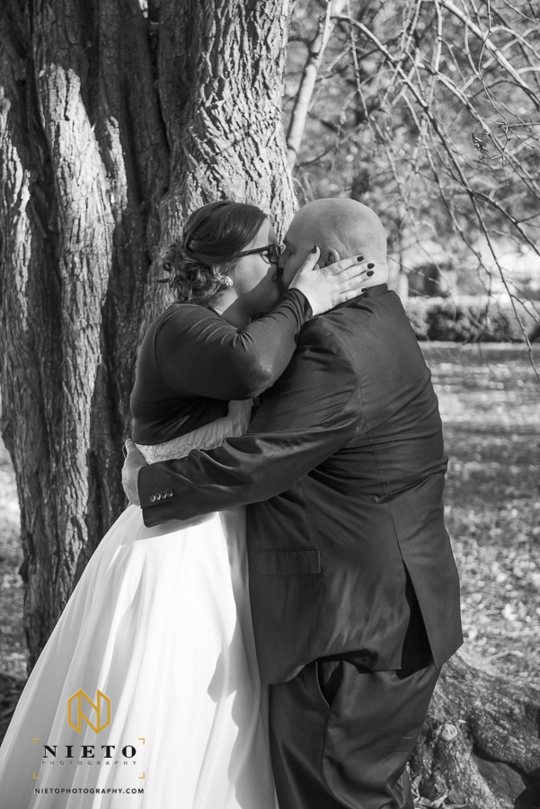 black and white image of the bride aggressively kissing the groom during their first look