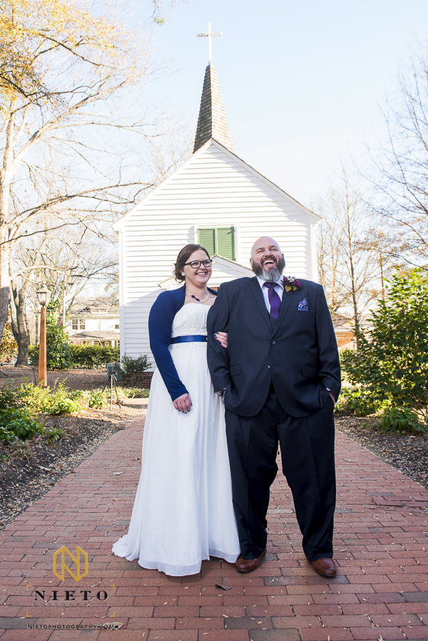 bride and groom laughing as they pose for a portrait in front of St Mark's Chapel before their Mordecai historic park wedding